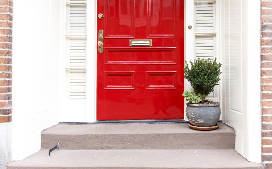 residence front entrance. sleek design. red door and potted plant on the stairs